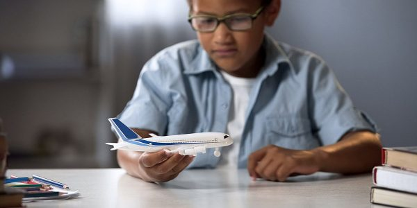Boy dreaming of becoming pilot of modern airline and flying to f